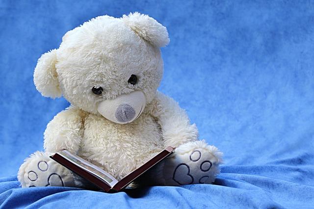 一人で本を読むクマのぬいぐるみ