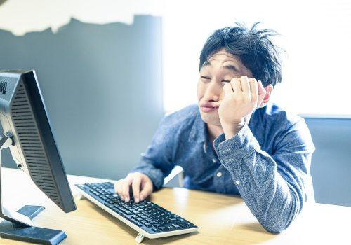 パソコンの前で疲れてる男性
